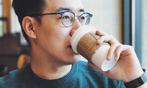 man drinking coffee in neighborhood cafe